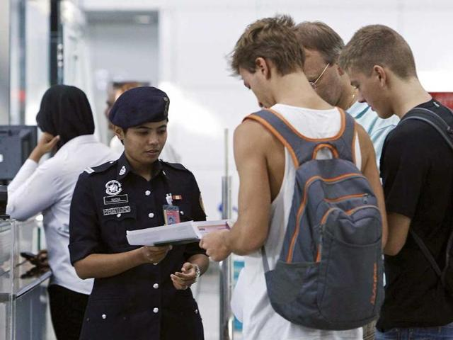 A customs officer checks the travel documents and passports of passengers at Kuala Lumpur International Airport in Sepang. (Reuters)