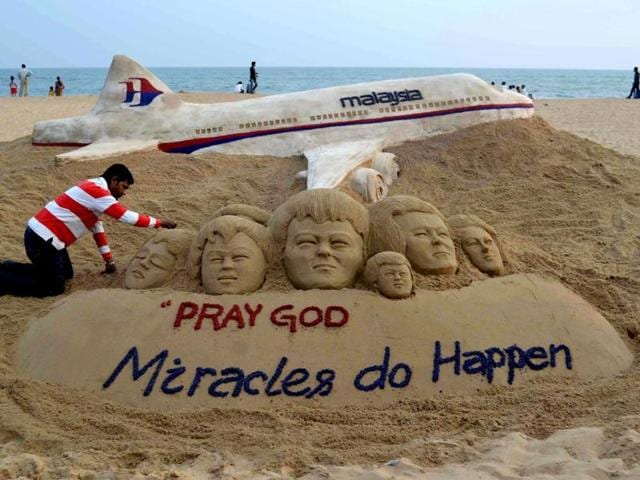 Indian-sand-artist-Sudersan-Pattnaik-gives-final-touches-on-a-sand-sculpture-with-a-message-of-prayers-for-the-missing-Malaysian-Airlines-flight-MH370-at-Puri-beach-Bhubaneswar-AFP-photo