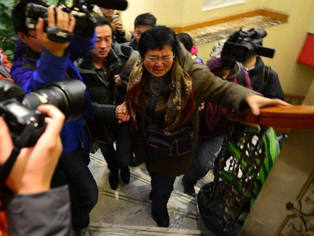 A-relative-C-of-a-passenger-who-was-travelling-on-board-the-missing-Malaysia-Airlines-MAS-flight-MH370-is-escorted-in-a-hotel-in-Beijing-AFP-photo