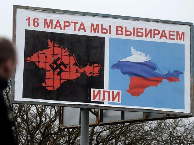 A-man-walks-passed-a-billboard-bearing-the-map-of-Crimea-with-a-Nazi-swastika-and-Russian-flag-reading-reading-March-16-we-choose-on-the-main-road-entering-the-Crimean-city-of-Sevastopol-AFP-Photo