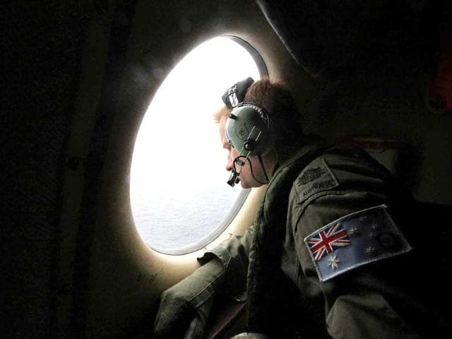 Royal Australian Air Force (RAAF) Warrant Officer Michal Mikeska looks out of a RAAF C-130J Hercules aircraft as it flies over the southern Indian Ocean during the search for the missing Malaysian Airlines flight MH370. REUTERS