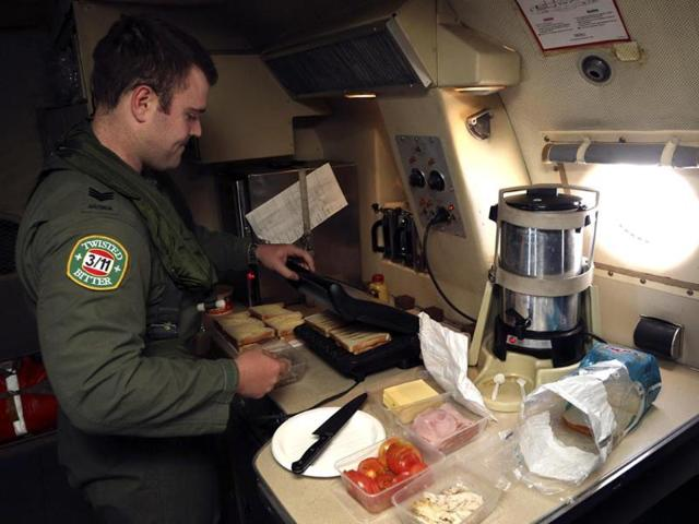 Sergeant Samuel Carson prepares meals for crew aboard a Royal Australian Air Force (RAAF) AP-3C Orion, as they search for missing Malaysian Airlines flight MH370 in the southern Indian Ocean. (Reuters)