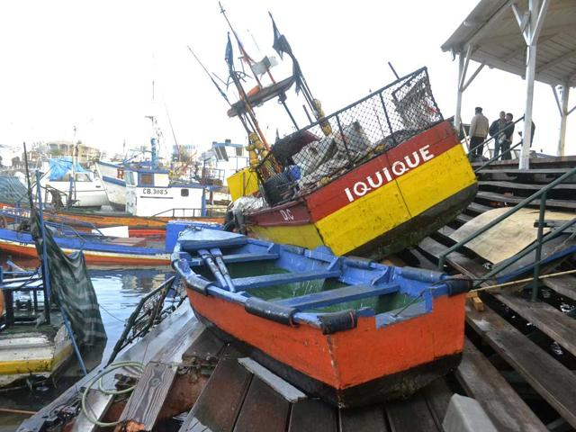 Fishermen-inspect-boats-washed-onto-a-dock-after-a-tsunami-hit-the-northern-port-of-Iquique-An-earthquake-with-a-magnitude-of-8-2-struck-off-the-coast-of-northern-Chile-near-the-copper-exporting-port-of-Iquique-killing-six-Reuters