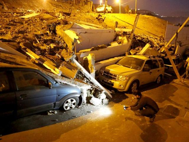 A-cameraman-records-near-cars-caught-under-rubble-after-an-earthquake-and-tsunami-hit-the-northern-port-of-Iquique-Reuters-photo
