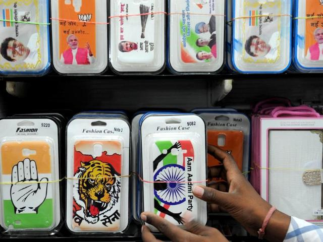 A-shopkeeper-peeps-out-from-behind-merchandise-with-political-symbols-at-his-shop-in-Kolkata-AFP-Photo
