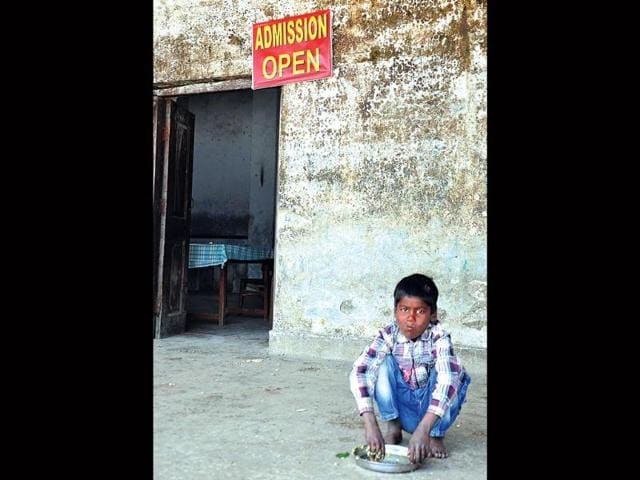 A-student-eats-his-mid-day-meal-while-an-admission-open-board-hangs-above-Kuldeep-Rana-HT-Photo