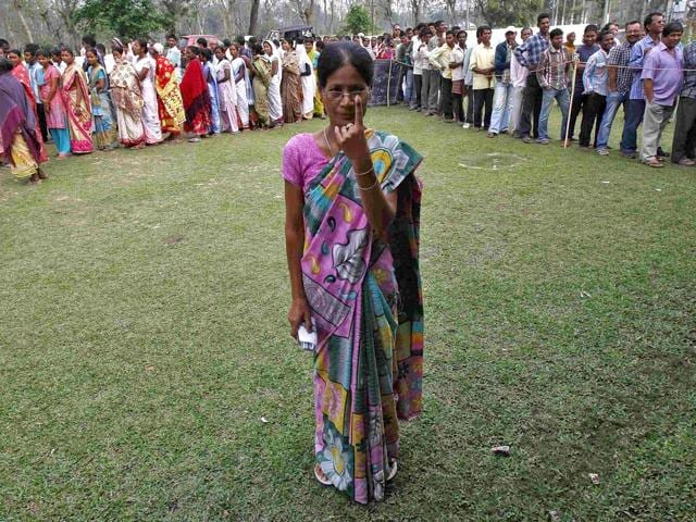 A-woman-shows-her-ink-marked-finger-after-casting-her-vote-as-others-line-up-to-cast-their-ballot-at-a-polling-station-in-Nakhrai-village-in-Tinsukia-district-Assam-Reuters-Photo