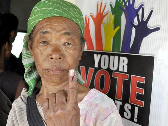 A Kashi tribeswoman displays her ink-marked finger after casting her ballot at a polling booth in Harleybagan village, Meghalaya (AFP Photo)