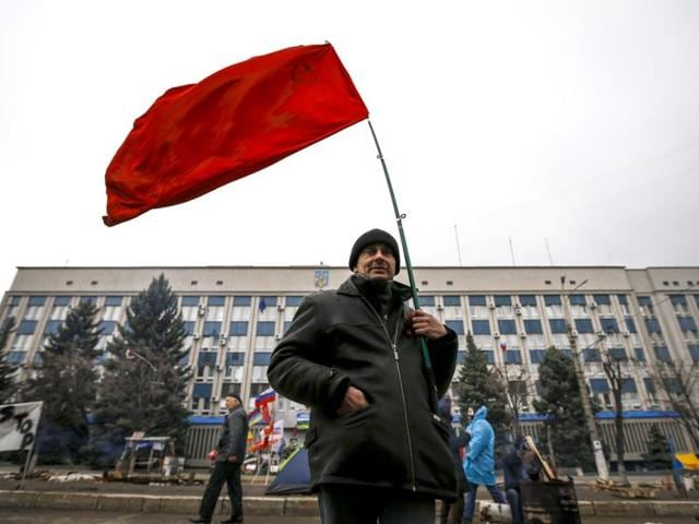 A-pro-Russian-supporter-holds-a-Soviet-flag-in-front-of-the-seized-office-of-the-SBU-state-security-service-in-Luhansk-in-eastern-Ukraine-Reuters-Photo