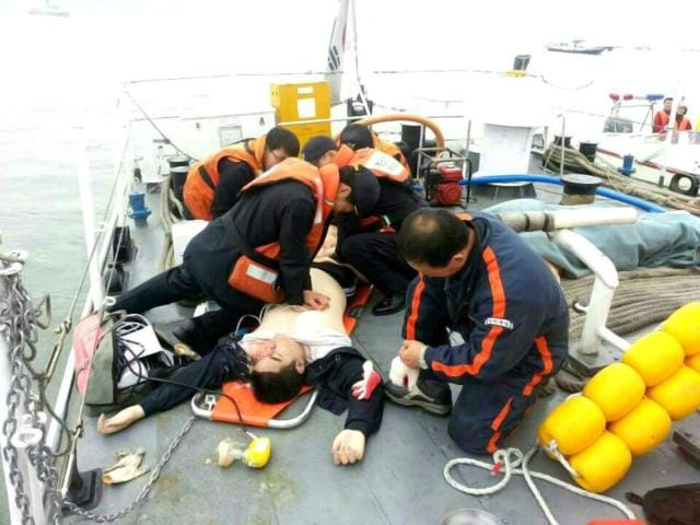 An injured passenger who was on a sinking ship, is rescued by South Korean maritime policemen, in the sea off Jindo . (Reuters Photo)