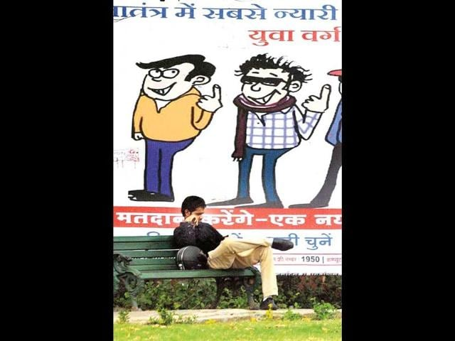 A-youngster-relaxes-beneath-a-hoarding-put-up-by-the-district-administration-to-create-voting-awareness-in-Jaipur-HT-Photo