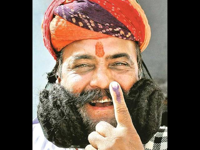 Girdhar-Vyas-who-has-a-17m-long-mustache-shows-his-ink-marked-finger-after-casting-his-vote-in-Bikaner-on-Thursday-PTI-Photo