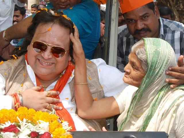 Singer-and-BJP-candidate-Bappi-Lahiri-seeks-blessings-from-an-elderly-woman-during-his-election-campaign-at-Bally-in-Sreerampore-Constituency-PTI-photo