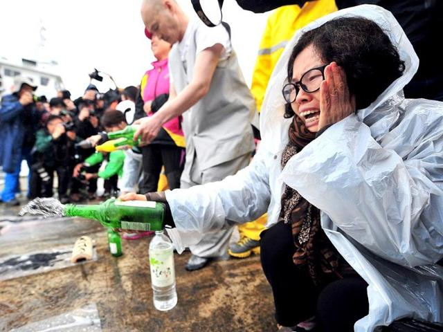 A South Korean relative (R) sprays alcohol as she prays for the missing passengers of a capsized ferry at a harbor in Jindo as South Korean rescue teams, including elite navy SEAL divers, raced to find up to 293 people missing, mostly high school students bound for a holiday island. (AFP photo)