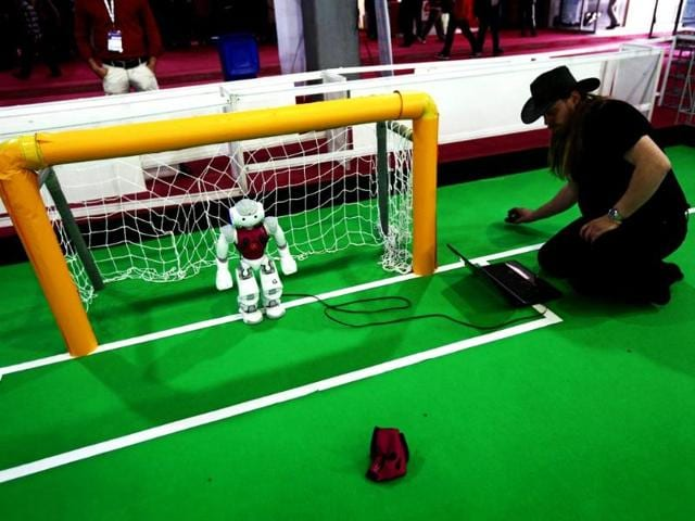 Nao-Team-Humboldt-from-Germany-checks-on-a-robot-to-prepare-it-for-a-match-during-the-RoboCup-Iran-Open-2014-in-Tehran-AFP-photo