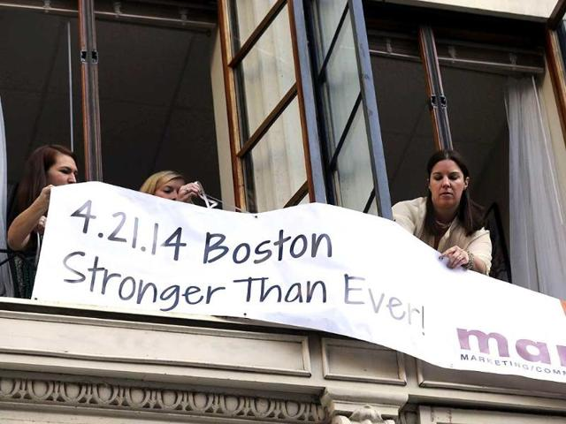 Marla-Fogelman-R-hangs-a-banner-on-the-second-floor-over-Marathon-Sports-store-the-site-of-the-first-bomb-blast-in-2013-before-the-start-of-the-118th-Boston-Marathon-AP-Photo