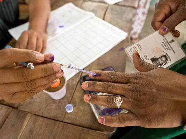A polling officer marks the finger of a woman voter at a polling booth in Gailpur in Alwar, Rajasthan. (AFP photo)