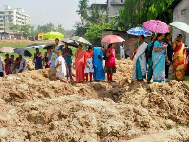 People standing in queue to cast their vote at Baghorbori area of Guwahati on Thursday. (PTI Photo)