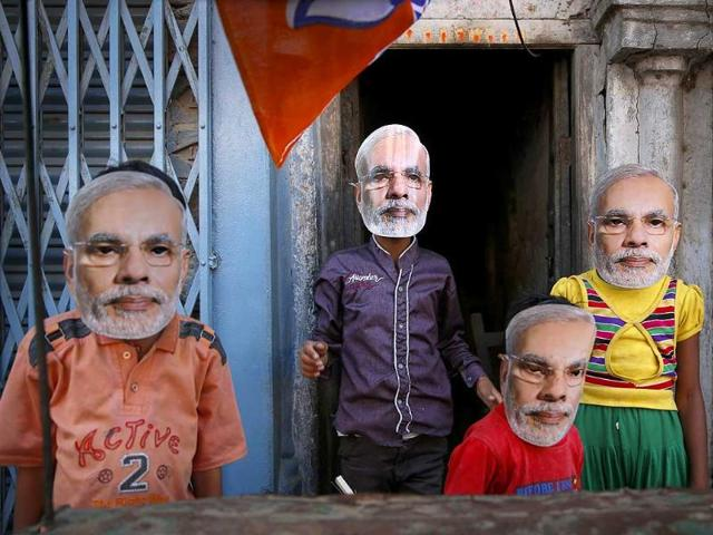 Children play wearing masks of BJP prime ministerial candidate Narendra Modi as he moves on a vehicle to file his nomination papers in Varanasi. (AP photo)