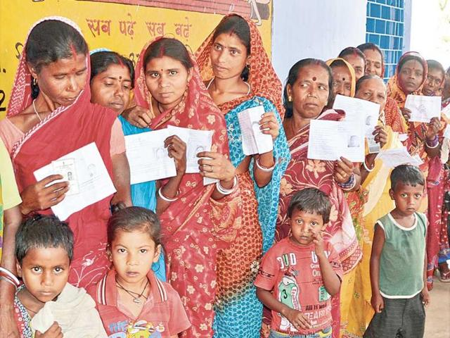 Women-voters-along-with-their-children-show-their-voter-identity-cards-at-Chandankiyari-block-s-booth-number-155-in-Bokaro-district-on-Thursday-Chandan-Paul-HT-Photo