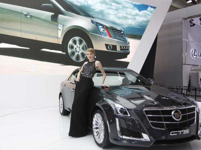 A-model-poses-by-a-Cadillac-CTS-car-at-the-China-International-Exhibition-Center-new-venue-during-the-Auto-China-2014-Beijing-International-Automotive-Exhibition-in-Beijing-on-April-21-2014-Photo-AFP