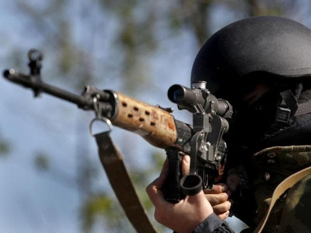 A-Ukrainian-government-soldier-aims-his-weapon-as-he-guards-a-checkpoint-near-the-village-of-Dolina-eastern-Ukraine-AP-photo