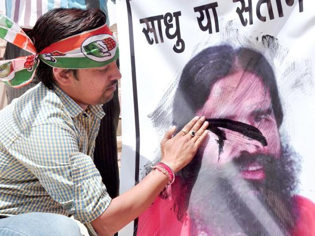 A-Congress-supporter-blackens-a-poster-of-yoga-guru-Ramdev-who-made-controversial-statements-on-Rahul-Gandhi-in-Bikaner-PTI-Photo