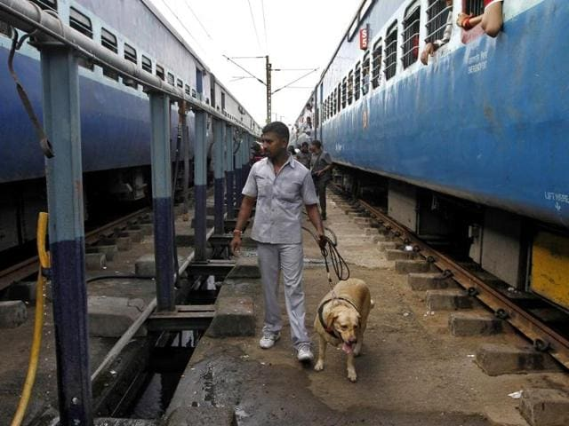 A member of a bomb disposal squad with a sniffer dog examines a passenger train in which two explosions occurred, at Chennai Central railway station. (Reuters photo)