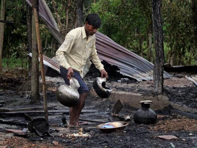 A-villager-salvages-utensils-from-a-burnt-house-after-the-area-was-set-on-fire-in-ethnic-violence-at-Khagrabari-village-in-the-northeastern-state-of-Assam-AP-Photo