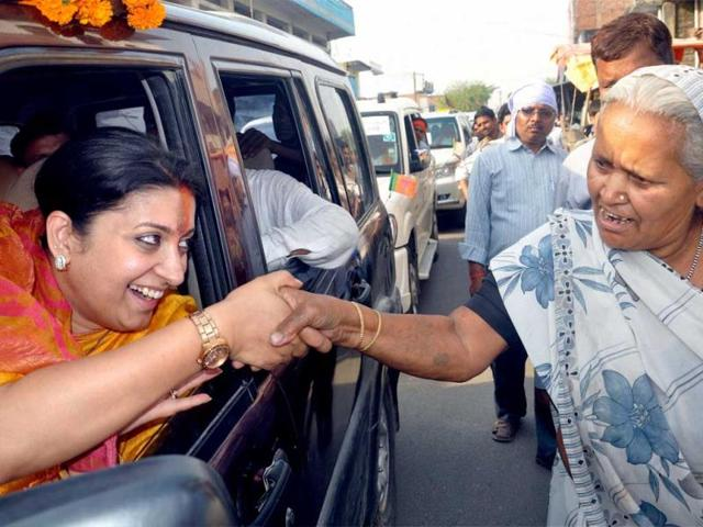 BJP candidate Smriti Irani shakes hands with a woman in Amethi.