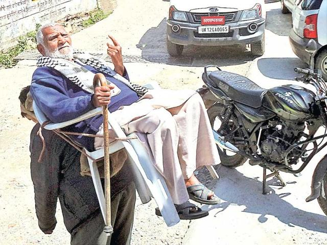An-old-man-being-lifted-after-casting-his-vote-in-Pauri-HT-Photo