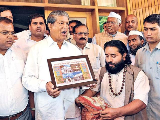 Chief-minister-Harish-Rawat-receives-a-portrait-of-Kedarnath-shrine-at-his-residence-in-Dehradun-on-Saturday-Rishi-Ballabh-HT-Photo