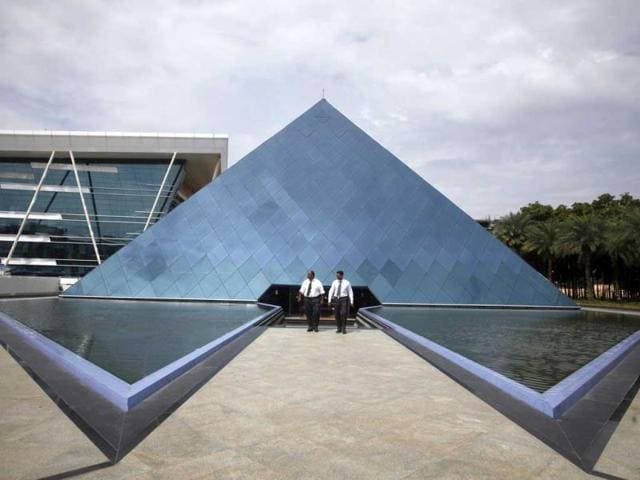 Employees-walk-in-front-of-a-pyramid-shaped-building-at-the-Infosys-campus-in-the-Electronic-City-area-of-Bangalore-Reuters-Photo