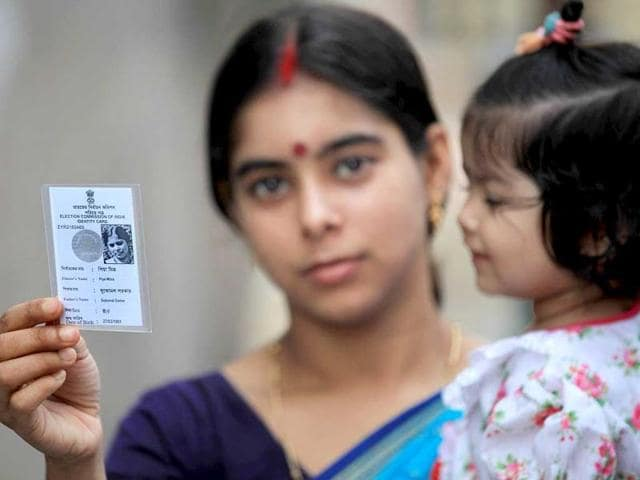 Voter Piya Mitra shows her voter card near a polling station during the ninth and final phase of the parliamentary elections in Kolkata. (EPA Photo)