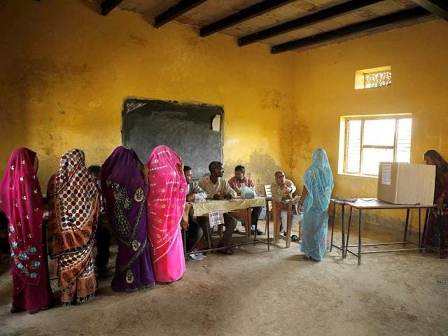 Women with their faces covered wait in a queue as another woman casts her vote on the final day of polling in Kunwarpur village, about 40 kilometers (25 miles) northwest of Jaunpur district. (AP Photo)