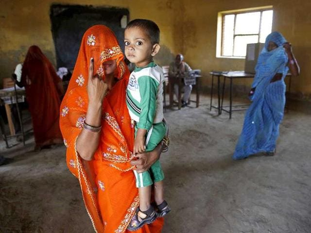 A woman carrying her child displays the indelible ink mark on her finger after casting her vote at a polling station in Kunwarpur village, about 40 kilometers northwest of Jaunpur district, Uttar Pradesh. (AP Photo)