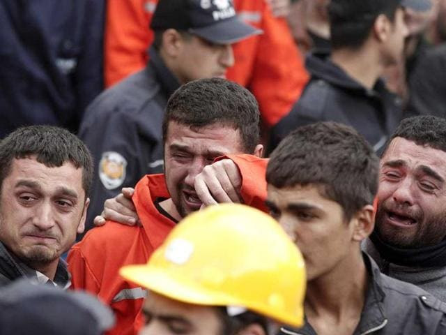 Relatives of miners who were killed or injured in a mine explosion react as rescuers work in Soma, a district in Turkey