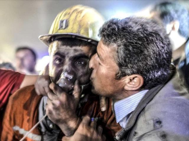 A man kisses his son, rescued from a Turkish mine after an explosion in a coal mine in Manisa. (AFP Photo)