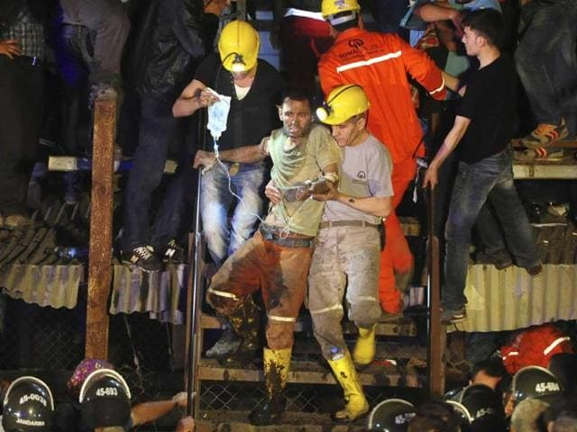 An injured miner is carried to an ambulance after being rescued from a coal mine he was trapped in, in Soma, a district in Turkey