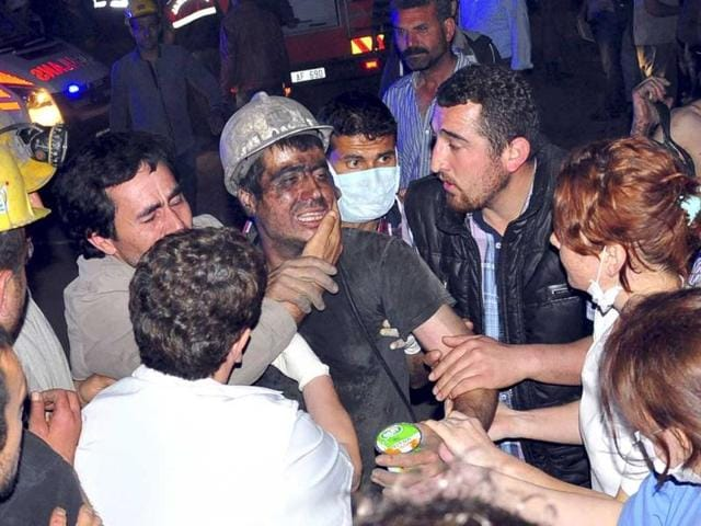 A rescued miner surrounded by relatives, medics and other miners cries after being rescued from a coal mine he was in trapped in Soma, a district in Turkey