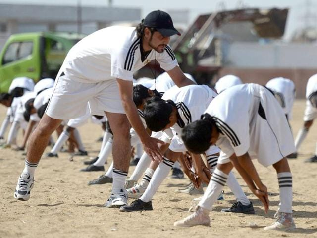 Pakistani academy coach Mohsin Shah (L) instructs local youth as they participate in a training session at a local stadium in Karachi. (AFP Photo)