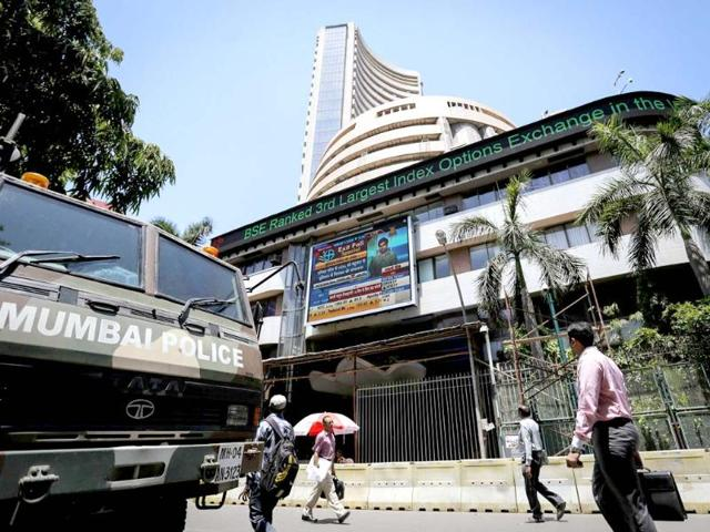 An-officegoer-walks-past-the-statue-of-the-bronze-Bull-outside-the-Bombay-Stock-Exchange-BSE-in-Mumbai-RBI-said-risks-to-the-growth-of-Asia-s-third-largest-economy-were-limited-after-the-US-credit-downgrade-that-has-spooked-global-markets