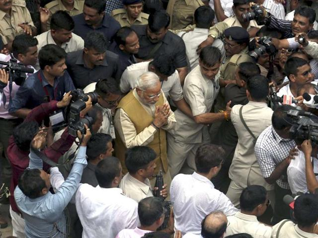 Bharatiya-Janata-Party-prime-ministerial-candidate-and-Gujarat-chief-minister-Narendra-Modi-is-seen-surrounded-by-security-and-media-persons-after-taking-blessings-from-his-mother-Heeraben-not-seen-at-his-brothers-residence-in-Gandhinagar--Agencies