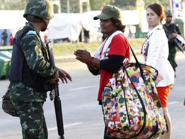 "A member of the pro-government ""red shirt"" group gives a traditional greeting to an armed Thai soldier at an encampment in Nakhon Pathom province on the outskirts of Bangkok (Reuters photo)"