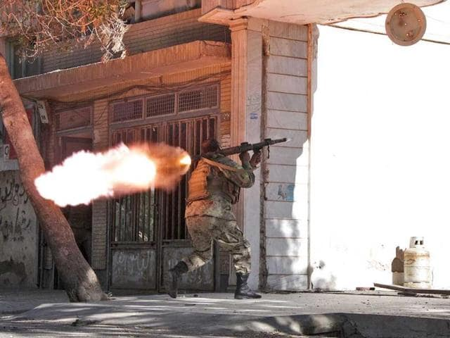 An Afghanistan National Army (ANA) soldier fires his weapon at the site of a clash between insurgents and security forces on the Indian Consulate in Herat. (AP Photo)