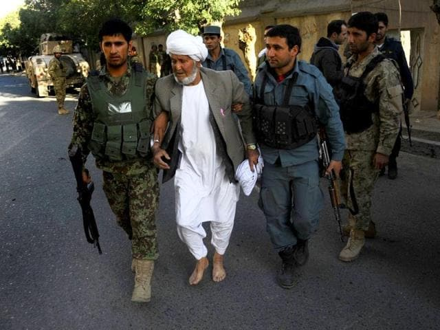 Afghan security forces escort a man away from the scene of an attack on the Indian consulate in Herat.  (AFP photo)