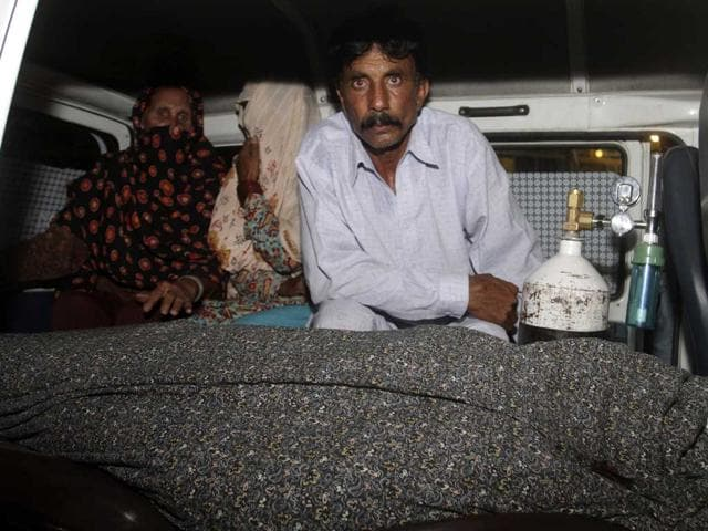 Mohammad-Iqbal-right-husband-of-Farzana-Parveen-sits-in-an-ambulance-next-to-the-body-of-his-pregnant-wife-who-was-stoned-to-death-by-her-own-family-in-Lahore-Pakistan-AP-Photo