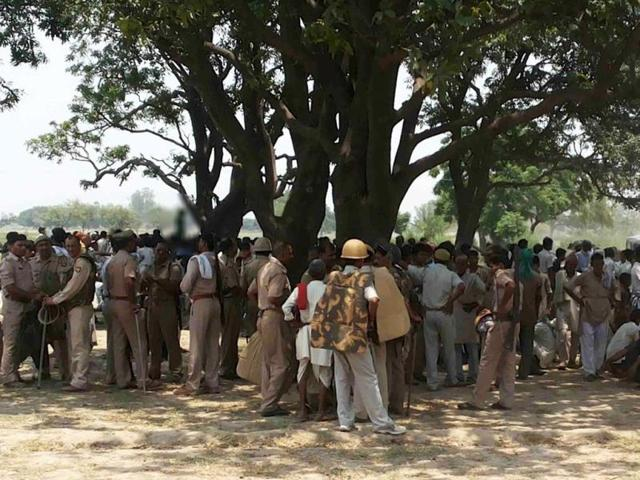 Villagers-and-policemen-gather-at-the-spot-where-two-teenage-cousins-were-found-hanging-from-a-mango-tree-in-Badaun-in-Uttar-Pradesh