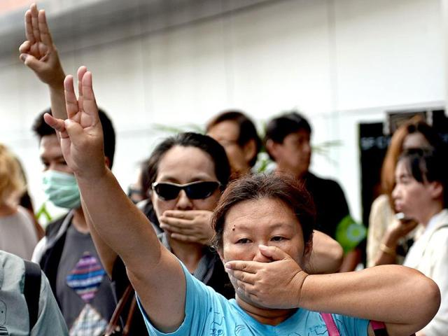 Anti-coup-protesters-flashing-a-three-finger-salute-during-a-gathering-at-a-shopping-mall-in-Bangkok-AFP-Photo