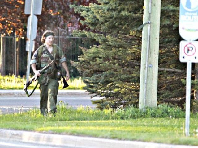 A-heavily-armed-man-that-police-have-identified-as-Justin-Bourque-walks-on-Hildegard-Drive-in-Moncton-New-Brunswick-June-4-2014-after-several-shots-were-fired-in-the-area-Three-police-officers-were-shot-dead-and-two-more-were-wounded-police-said-as-they-conducted-a-manhunt-for-a-man-carrying-a-rifle-and-wearing-camouflage-clothes-Police-said-they-were-searching-for-Justin-Bourque-24-of-Moncton-Reuters-Photo
